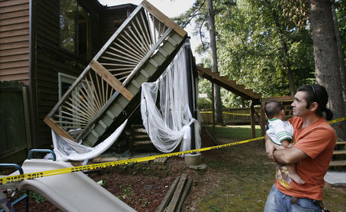 Image of father holding baby by a collapsed deck